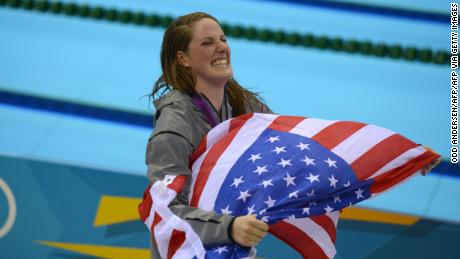 Franklin carries a US flag from the podium after recieving her gold medal for the women's 100-meter backstroke final at the London 2012 Olympic Games.