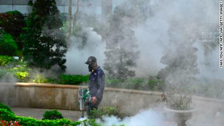 A mask-clad worker disinfects a park to prevent the spread of the coronavirus in New Taipei City on March 9.