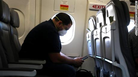 A passenger looks at his phone while waiting aboard a United Airlines plane before taking off from George Bush Intercontinental Airport on May 11, 2020 in Houston, Texas.