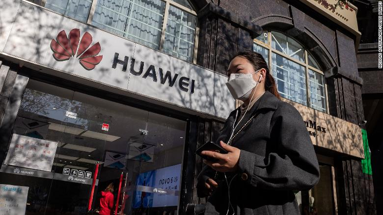 A woman wearing a face mask amid concerns over the Covid-19 coronavirus walks holding her smartphone past a Huawei shop (L) on a street in Beijing on April 22, 2020.