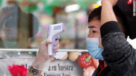 Amid concerns of the spread of COVID-19, Ronaldo Santos has his temperature checked before starting his work shift in the meat department of a grocery store in Dallas on May 12, 2020.