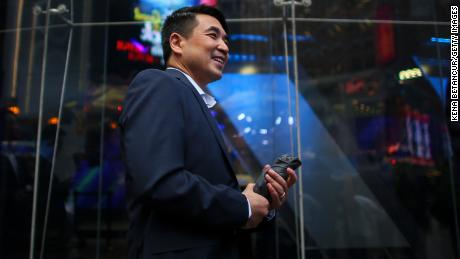 Zoom founder Eric Yuan poses in front of the Nasdaq building as the screen shows the logo of the video-conferencing software company Zoom after the opening bell ceremony on April 18, 2019 in New York City. The video-conferencing software company announced it's IPO priced at $36 per share, at an estimated value of $9.2 billion. (Photo by Kena Betancur/Getty Images)