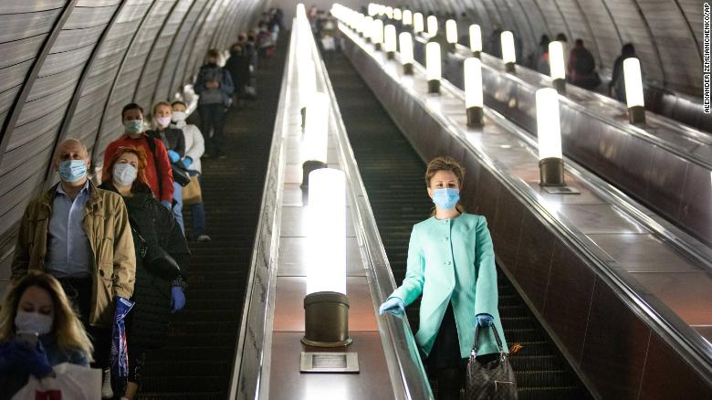 People wearing face masks and gloves on a subway escalator in Moscow on Tuesday.