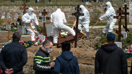 Grave diggers bury a COVID-19 victim as relatives and friends stand at a safe distance, at a cemetary in Kolpino, outside St. Petersburg, on Friday.