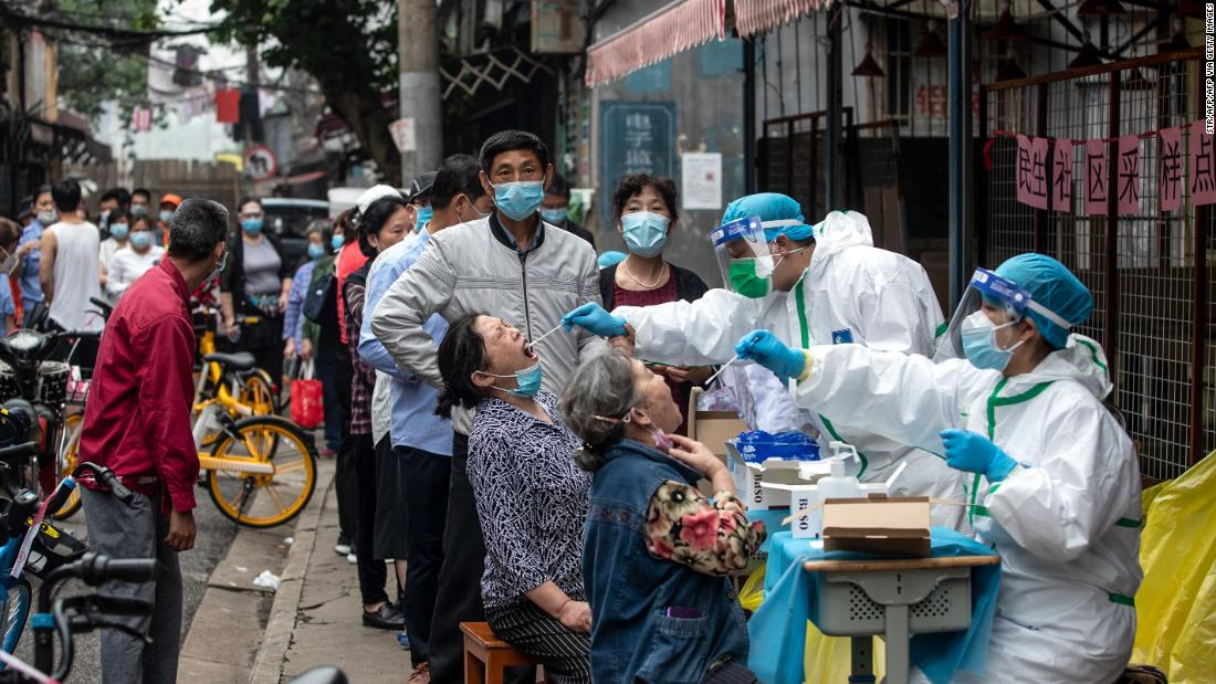TOPSHOT - Medical workers take swab samples from residents to be tested for the COVID-19 coronavirus in a street in Wuhan in China's central Hubei province on May 15, 2020. - Authorities in the pandemic ground zero of Wuhan have ordered mass COVID-19 testing for all 11 million residents after a new cluster of cases emerged over the weekend. (Photo by STR / AFP) / China OUT (Photo by STR/AFP via Getty Images)