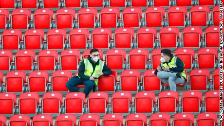 Stewards wearing protective face masks sit in the vacant stands at Union Berlin's home stadium, with all Bundesliga matches until the end of the season being played behind closed doors.