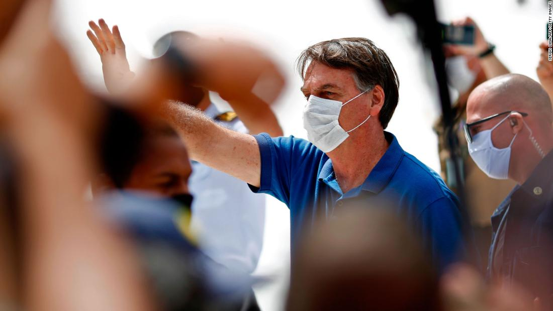 Brazilian President Jair Bolsonaro (C) waves to supporters duering a rally in Brasilia on May 17, 2020, amid the novel coronavirus pandemic. - Brazil's COVID-19 death toll passed 15,000 on Saturday, official data showed, while its number of infections topped 230,000, making it the country with the fourth-highest number of cases in the world. (Photo by Sergio LIMA / AFP) (Photo by SERGIO LIMA/AFP via Getty Images)