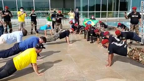 Bolsonaro (left, blue shirt) does push-ups at an event in Brasilia on Sunday.