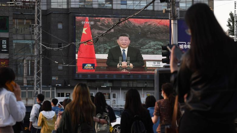 Chinese President Xi Jinping speaking via video link to the World Health Assembly, on a giant screen beside a street in Beijing on May 18, 2020.