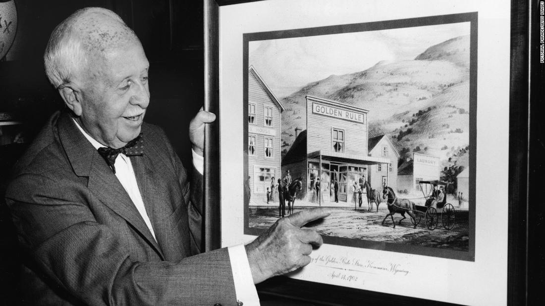 "Businessman James Cash Penney points to a picture of his first store in Kemmerer, Wyoming. JCPenney started in 1902 as a dry-goods store called the Golden Rule Store. At the time, Penney's business practices were revolutionary. He banned haggling, a common practice at the time, to keep prices low. And he encouraged his employees to ""serve the public to its ultimate satisfaction."" The company changed its name a decade later, opened many more stores and went public in 1929."