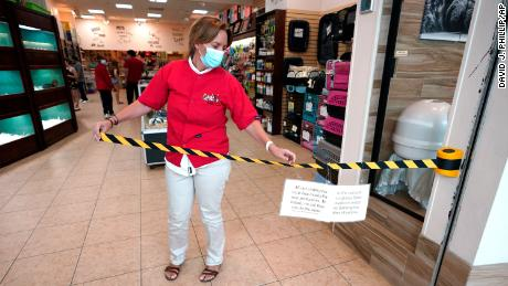 Store manager Natalie Hijazi temporarily closes off the entrance to a Pet Fair store inside The Woodlands Mall to help meet the current occupancy limits in place Tuesday, May 5, 2020, in The Woodlands, Texas. The mall reopened Tuesday with increased health and safety measures in place.Texas' stay-at-home orders due to the COVID-19 pandemic have expired and Texas Gov. Greg Abbott has eased restrictions on many businesses that have now opened.