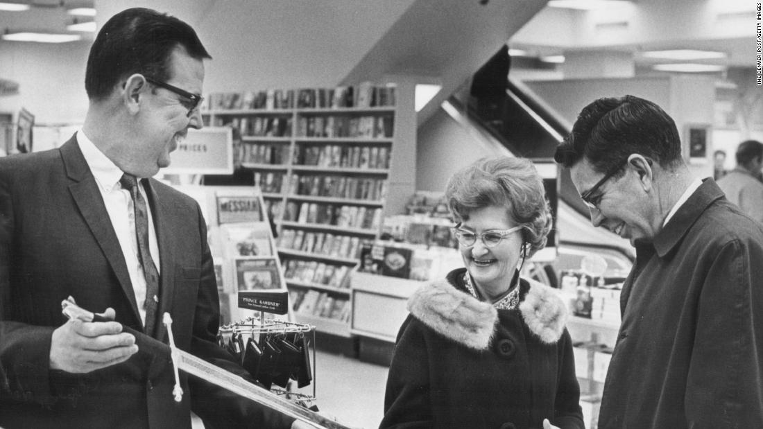 Russell Martin, a store manager in Denver, shows a sword to a couple that won it as a special promotion in 1968.