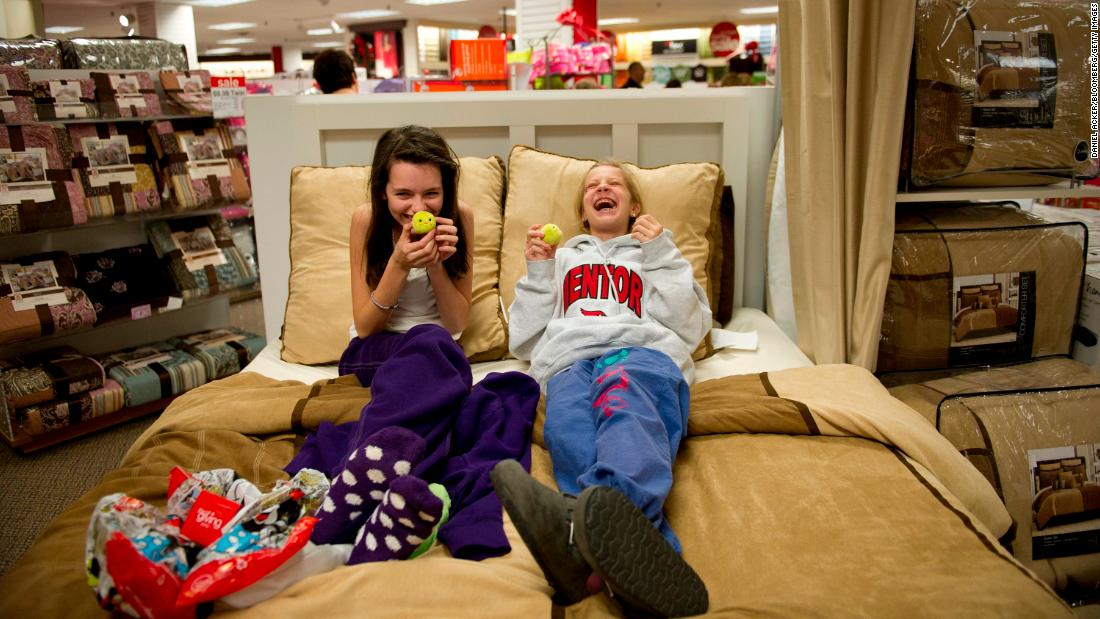 Gabbie Juka, left, and Allison Funk share a laugh as they relax on a bed at a JCPenney store in Mentor, Ohio, in 2010.