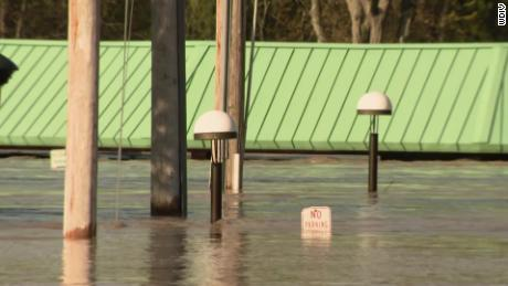 Floodwaters flow through a part of downtown Midland on Wednesday morning, close to a farmers' market with a green roof.