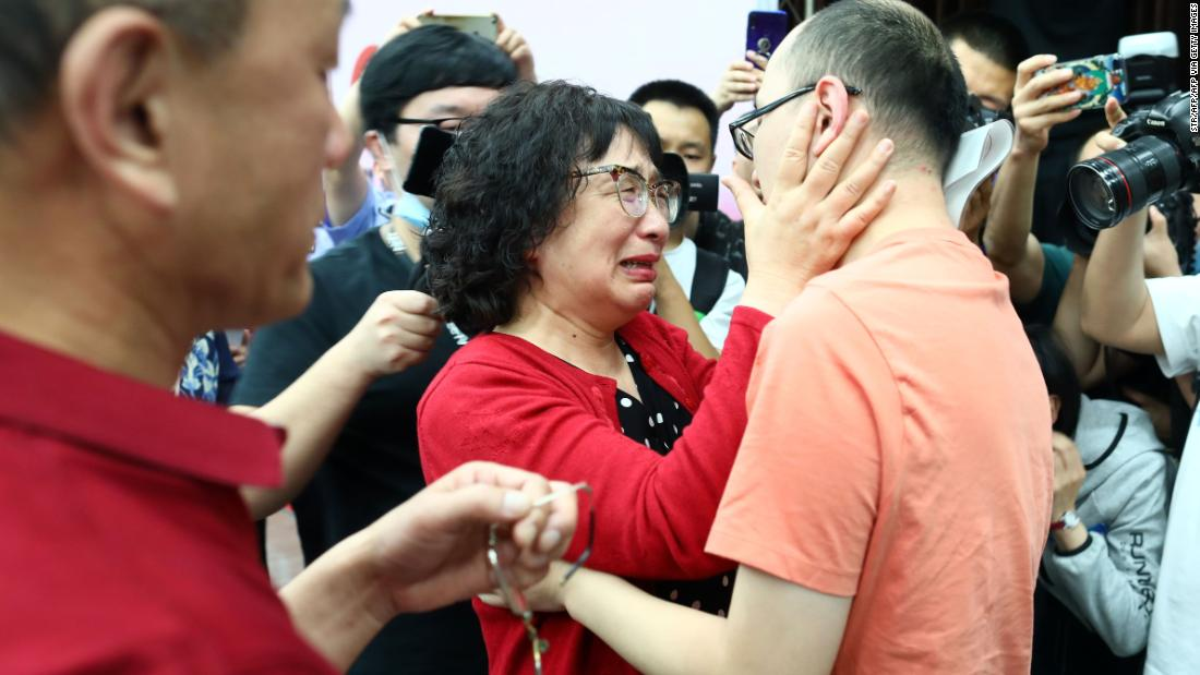 This photo taken on May 18, 2020 shows Mao Yin (R) reuniting with his mother Li Jingzhi (C) and father Mao Zhenping (L) in Xian, in China's northern Shaanxi province. - A Chinese man who was kidnapped as a toddler 32 years ago has been reunited with his biological parents, after police used facial recognition technology to track him down. (Photo by STR / AFP) / China OUT (Photo by STR/AFP via Getty Images)