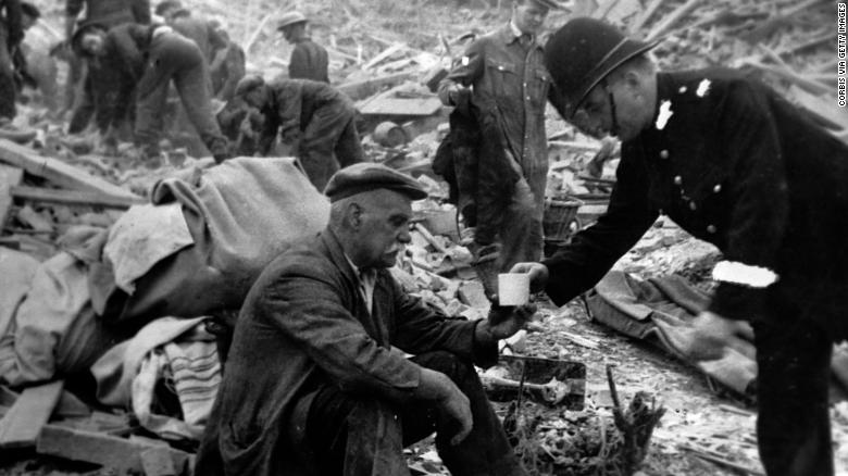 A British police officer hands a victim tea in the middle of the bombing wreckage during World War II.
