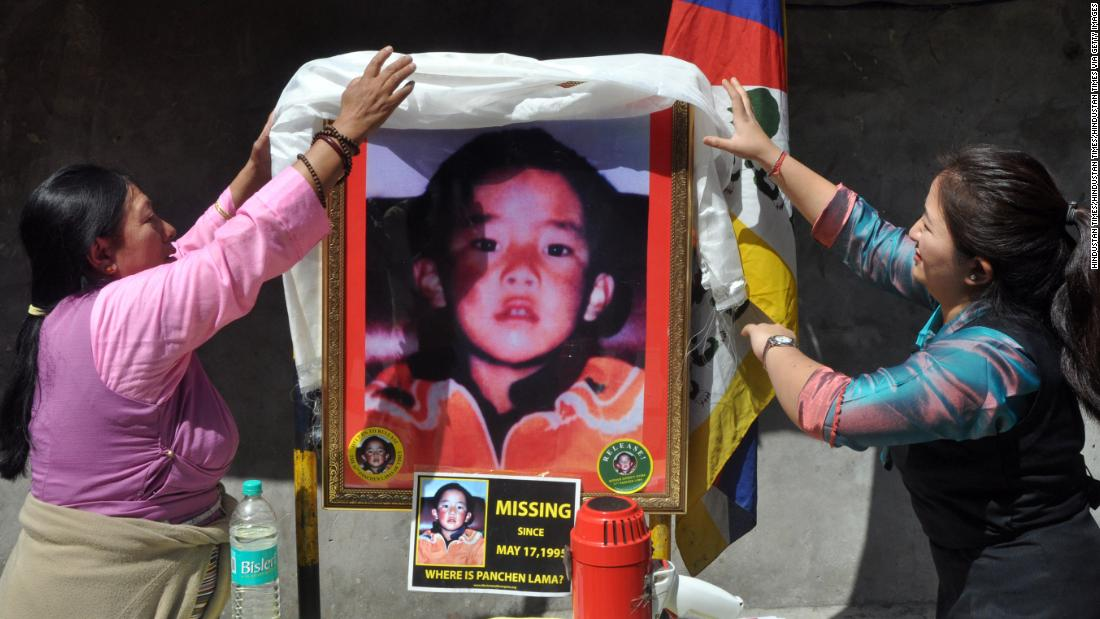Tibetans stand next to a portrait showing the last know image of Gedhun Choekyi Nyima, on April 25, 2017 in Mcleodganj near Dharamsala, India.