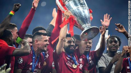 Salah raises the Champions League trophy.
