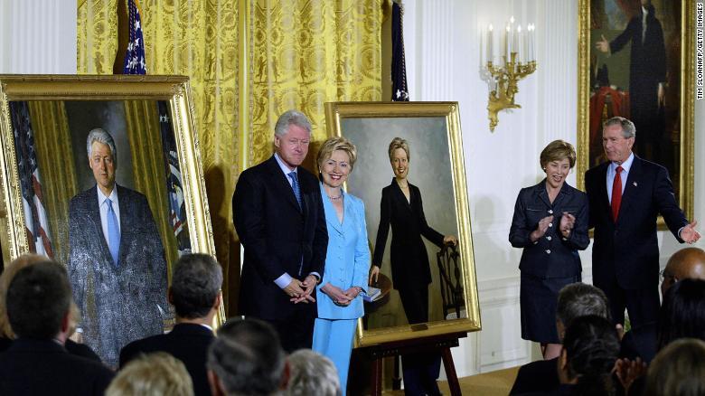 Бывший президент Билл Клинтон и бывшая первая леди Хиллари Клинтон поддерживают свои официальные портреты в Белом доме во время церемонии открытия, организованной тогдашним президентом Джорджем Бушем и первой леди Лорой Буш в июне 2004 года в Белом доме.