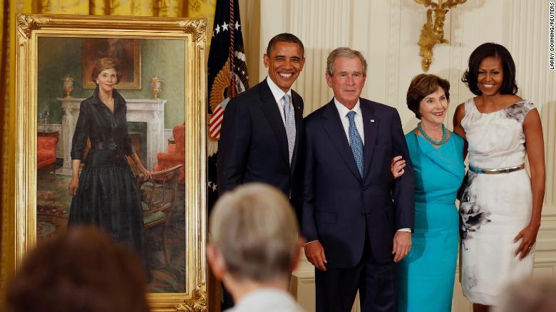Бывший президент Джордж Буш стоит рядом с тогдашним президентом Бараком Обамой, в то время как бывшая первая леди Лора Буш стоит рядом с тогдашней первой леди Мишель Обамой во время обнародования их официальных портретов Белого дома в Восточной комнате Белого дома в мае 2012 года.