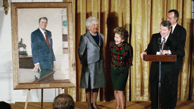 Бывший президент Рональд Рейган и бывшая первая леди Нэнси Рейган смотрят на портрет бывшего президента вместе с тогдашним президентом Джорджем Бушем-старшим и тогда еще первой леди Барбарой Буш во время церемонии открытия в Белом доме в ноябре 1989 года.