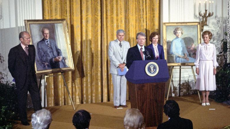 Президент Джимми Картер делает замечания по поводу обнародования портретов бывшего президента Джеральда Р. Форда и бывшей первой леди Бетти Форд в восточной комнате Белого дома в августе 1980 года.