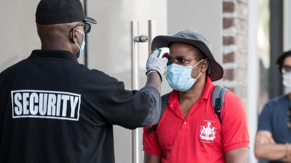 CHARLESTON, SC - MAY 13: A security guard takes the temperature of a customer outside the Apple Store on May 13, 2020 in Charleston, South Carolina. Customers had their temperatures taken and were required to wear masks at the South Carolina store, as locations in Idaho, Alabama, and Alaska reopened as well following forced closures due to the coronavirus. (Photo by Sean Rayford/Getty Images)