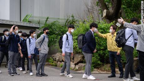Gli studenti che indossano maschere facciano il controllo della temperatura all'arrivo alla Keongbok High School di Seoul il 20 maggio 2020.