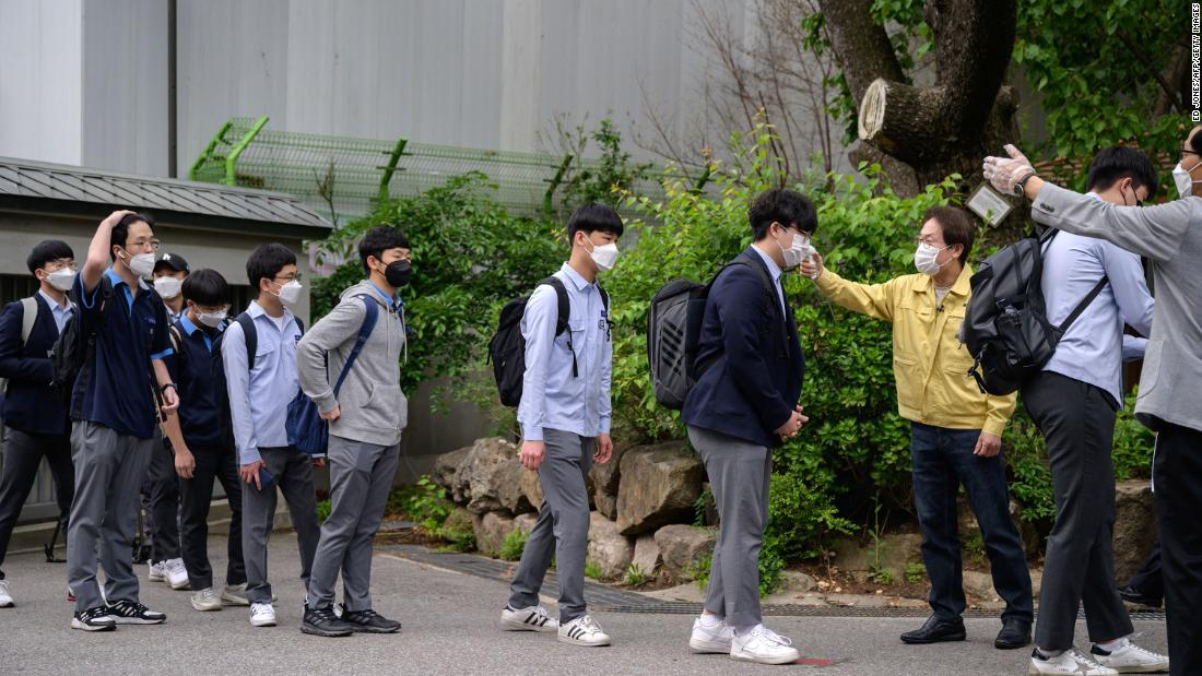 Students wearing facemasks amid concerns over the COVID-19 novel coronavirus undergo a temperature check as they arrive at Keongbok High School in Seoul on May 20, 2020. - Hundreds of thousands of South Korean students returned to classes as schools started reopening after more than a two-month delay over the coronavirus outbreak. (Photo by Ed JONES / AFP) (Photo by ED JONES/AFP via Getty Images)