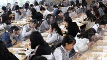 I dottorandi pranzano ai tavoli con barriere di plastica per prevenire la possibile diffusione del coronavirus nella caffetteria della Jeonmin High School di Daejeon, Corea del Sud, mercoledì 20 maggio 2020.