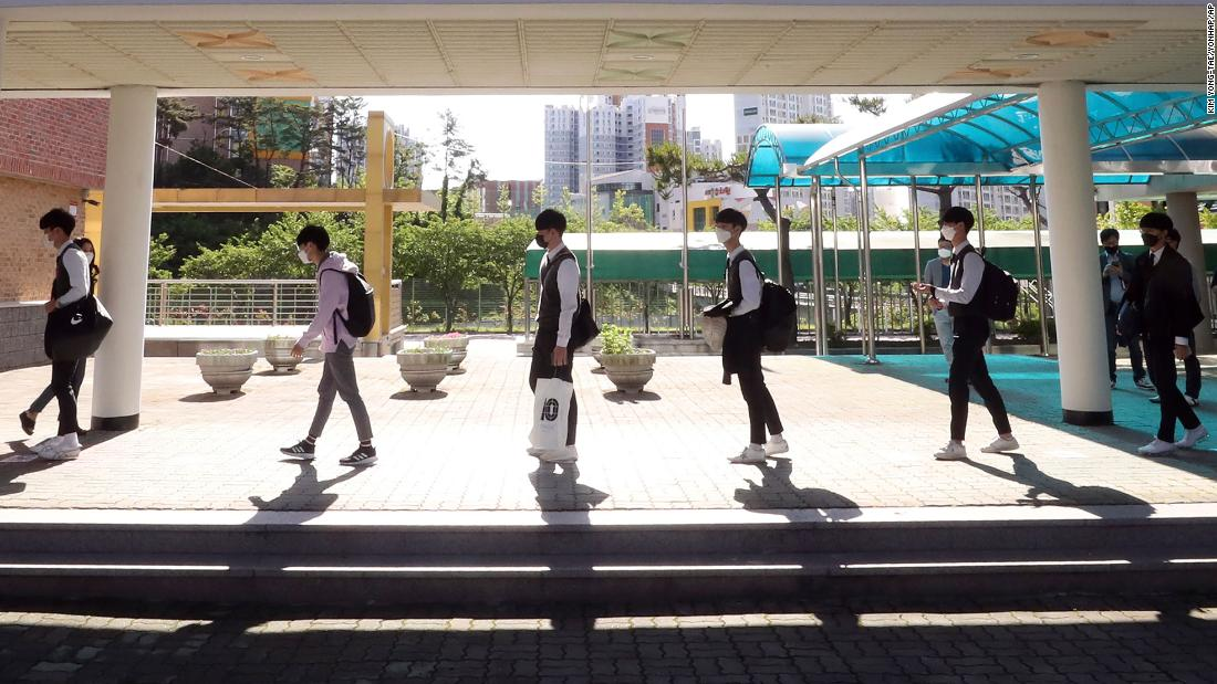 Senior students maintain social distancing as they arrive at Hamwol High School in Ulsan, South Korea, Wednesday, May 20, 2020.