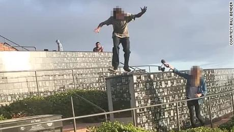 A skateboarder in California caused controversy on Monday after a video surfaced of him riding across the sacred walls of a memorial honoring military members. CNN obscured parts of this image to protect the identities of the pictured individuals.