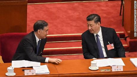 Chinese President Xi Jinping (R) speaks with Politburo Standing Committee member Wang Yang (L) during the opening session of the National People's Congress (NPC) at the Great Hall of the People in Beijing on May 22, 2020. - China took the rare move of not setting an annual growth target this year after the coronavirus battered the world's second-largest economy and ravaged global growth, Premier Li Keqiang said on May 22. (Photo by Leo RAMIREZ / AFP) (Photo by LEO RAMIREZ/AFP via Getty Images)