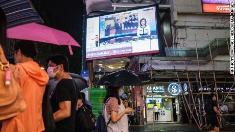I pedoni camminano sotto uno schermo televisivo a Hong Kong il 21 maggio 2020, mostrando una notizia di Pechino trasmessa dal presidente cinese Xi Jinping (C) alla Conferenza consultiva politica del popolo cinese.