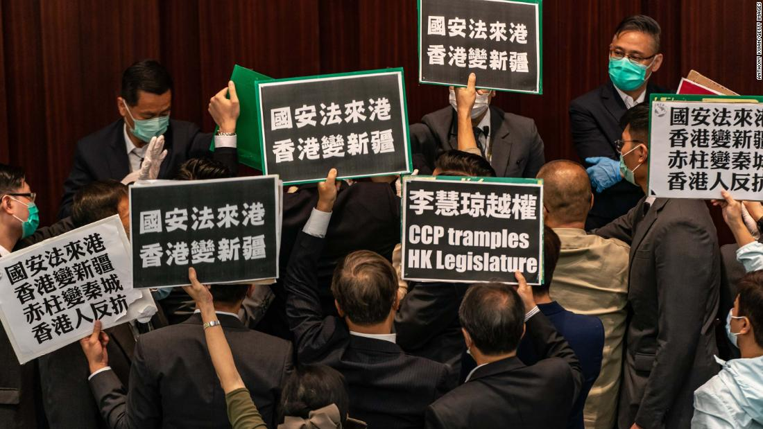 HONG KONG, CHINA - MAY 22:  Pro-democracy lawmakers hold placards to protest against the pro-Beijing lawmakers at the House Committee's election of vice chairpersons, presided by pro-Beijing lawmaker Starry Lee Wai-King at the Legislative Council on May 22, 2020 in Hong Kong, China. Chinese Premier Li Keqiang said on Friday during the National People's Congress that Beijing would establish a sound legal system and enforcement mechanism for safeguarding national security in Hong Kong. (Photo by Anthony Kwan/Getty Images)