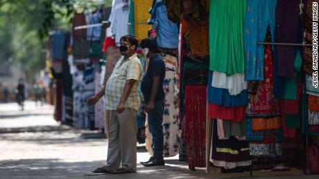 Vendors wait for customers in front of their clothing shops in a market area after the government eased restrictions imposed as a preventive measure against the spread of the COVID-19 coronavirus in New Delhi on May 20, 2020. (Photo by Jewel SAMAD / AFP) (Photo by JEWEL SAMAD/AFP via Getty Images)