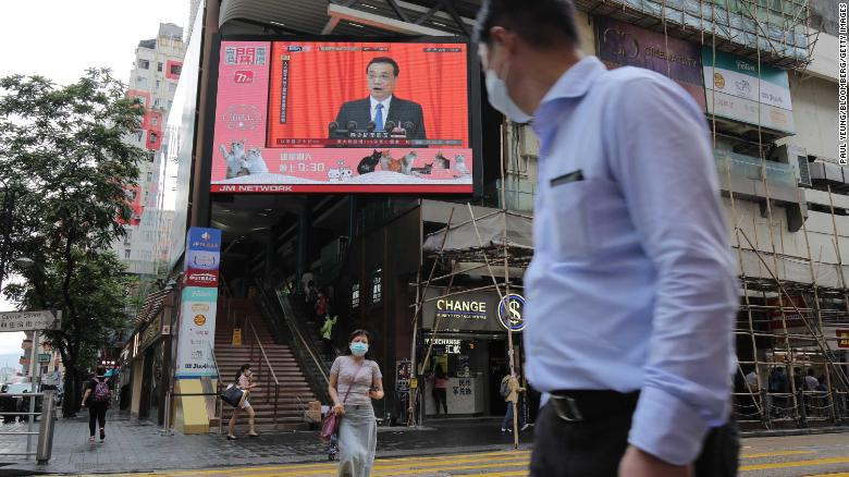 Pedestrians in Hong Kong wearing protective masks walk past a screen playing a news report on Chinese Premier Li Keqiang speaking at the National People's Congress on Friday.