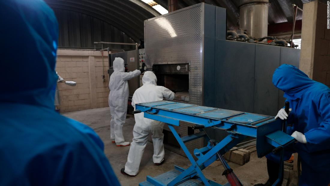 Workers wear protective gear as they start a cremation oven in Ecatepec, Mexico, on May 21.