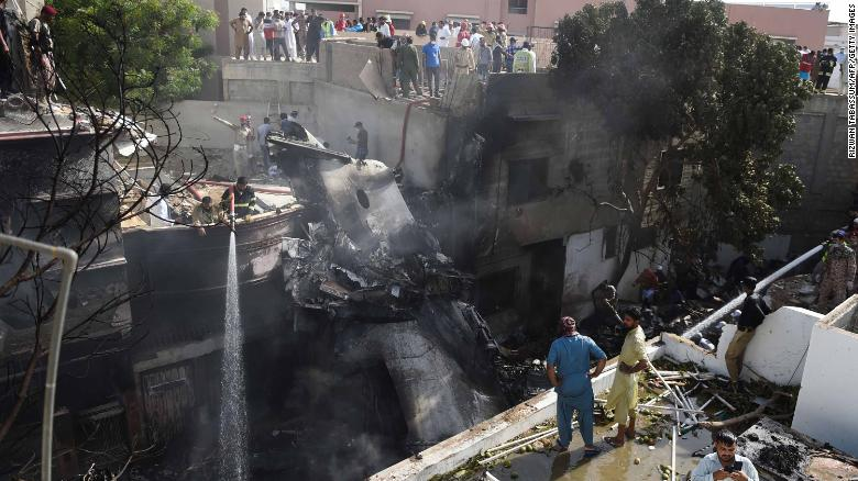 Firefighters spray water on the wreckage of a Pakistan International Airlines aircraft after it crashed in a residential area of Karachi, Pakistan, on Friday, May 22.
