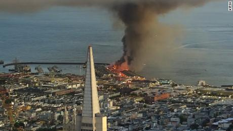 Pier 45 burns in San Francisco, with the Transamerica Pyramid in the foreground.