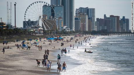 People walk and gather  along the beach on Saturday morning in Myrtle Beach, South Carolina.