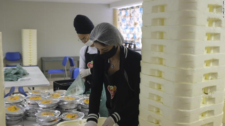 Volunteers prepare some of the 10,000 meals that are handed out to residents of the Paraisopolis favela each day, so they don't need to leave their houses to eat.