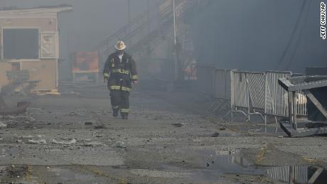 A fire official walks near the site of the Pier 45 fire on Saturday.