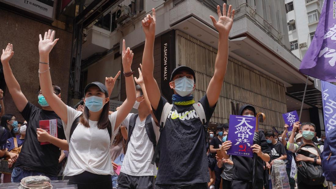 "Protesters gesture with five fingers, signifying the ""Five demands - not one less"" as they march along a downtown street during a pro-democracy protest against Beijing's national security legislation in Hong Kong, Sunday, May 24, 2020. Hong Kong's pro-democracy camp has sharply criticised China's move to enact national security legislation in the semi-autonomous territory. They say it goes against the ""one country, two systems"" framework that promises the city freedoms not found on the mainland."