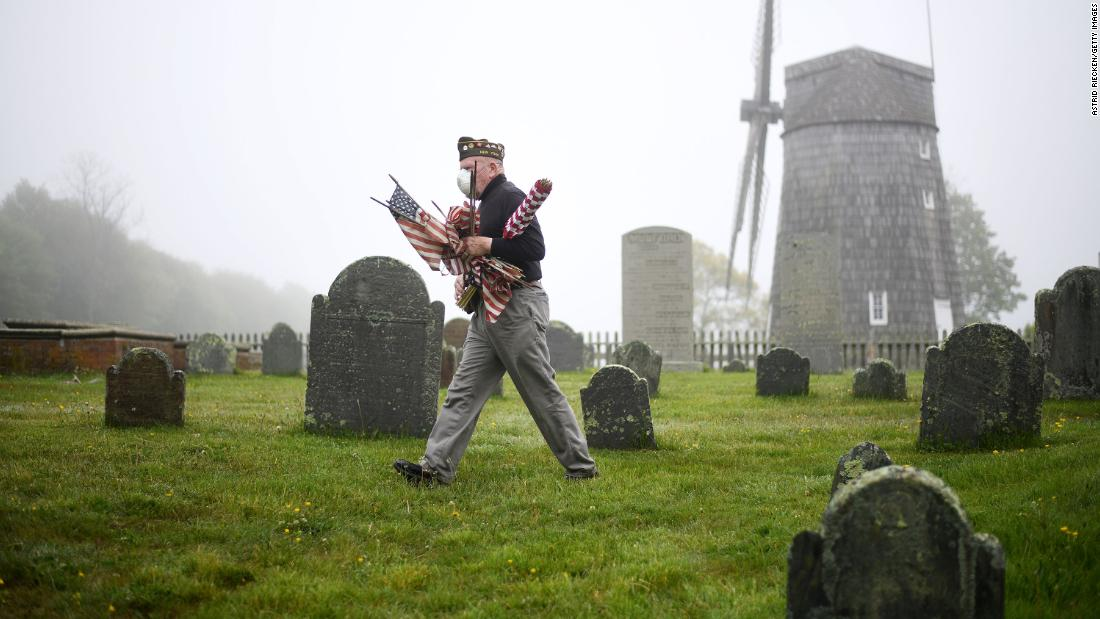 Retired US Marine Corps veteran Brian Carabine replaces flags at the South End Cemetery in East Hampton, New York, on May 23 ahead of Memorial Day weekend.