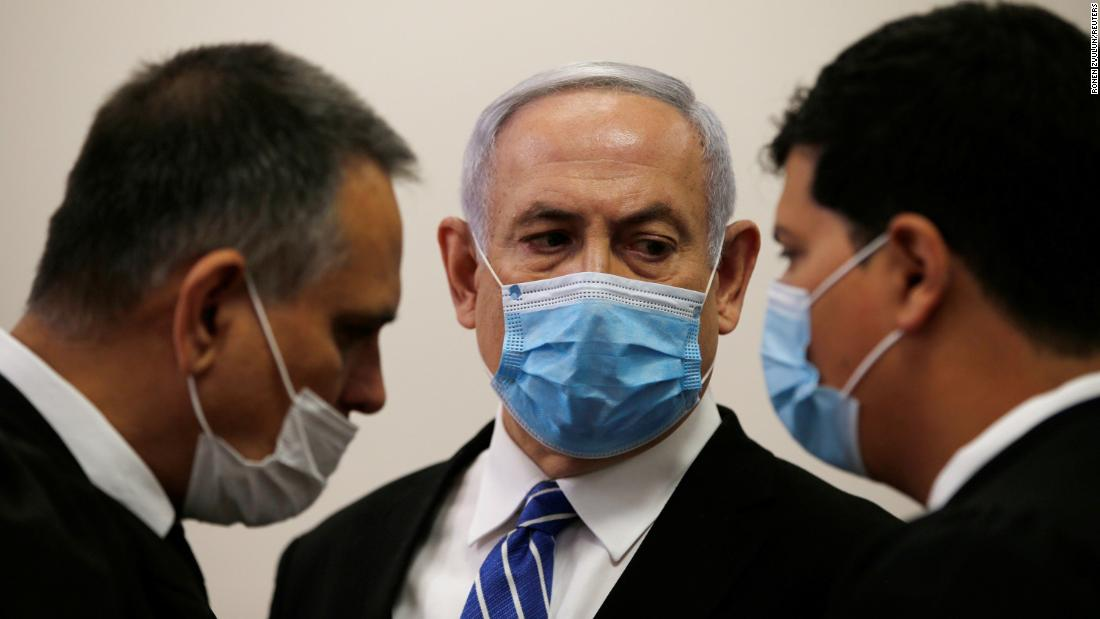 Israeli Prime Minister Benjamin Netanyahu, wearing a face mask, looks at his lawyer while standing inside the court room as his corruption trial opens at the Jerusalem District Court May 24, 2020. REUTERS/Ronen Zvulun