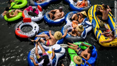 A group of people float on connected inflatables down the American River near Rancho Cordova, California, on Memorial Day Weekend.