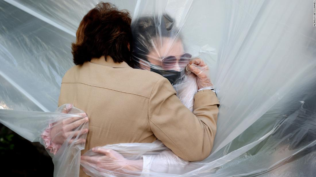 Olivia Grant (R) hugs her grandmother, Mary Grace Sileo through a plastic drop cloth hung up on a homemade clothes line during Memorial Day Weekend on May 24, 2020 in Wantagh, New York.  It is the first time they have had contact of any kind since the coronavirus COVID-19 pandemic lockdown started in late February.