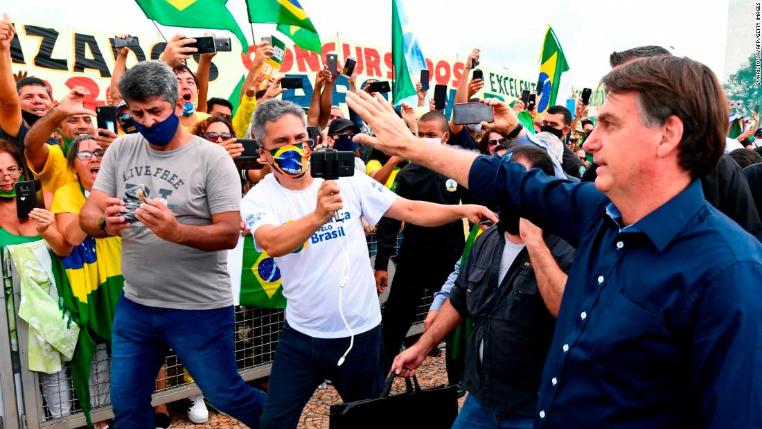 Brazil's President Jair Bolsonaro greets supporters upon arrival at Planalto Palace in Brasilia, on May 24, 2020, amid the COVID-19 coronavirus pandemic. - Despite positive signs elsewhere, the disease continued its surge in large parts of South America, with the death toll in Brazil passing 22,000 and infections topping 347,000, the world's second-highest caseload. (Photo by EVARISTO SA / AFP) (Photo by EVARISTO SA/AFP via Getty Images)