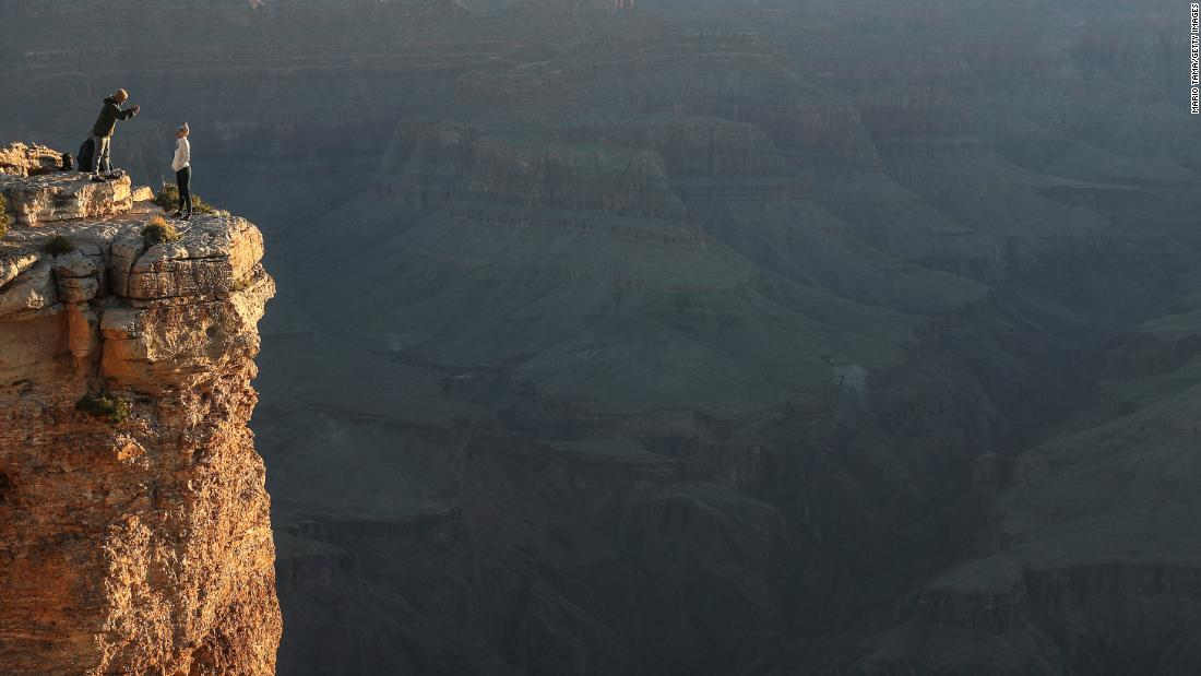 Visitors take photos after sunrise on Memorial Day from the South Rim ofGrand Canyon National Park, which has partially reopened on weekends amid the coronavirus (COVID-19) pandemic, on May 25, 2020 in Grand Canyon National Park, Arizona. The park has opened for limited hours and access the past two weekends despite concerns that the mingling of visitors could contribute to the spread of the COVID-19 virus.  Critics point out that the neighboring Navajo Nation is currently suffering the highest rate of COVID-19 infection in the nation per capita and some travelers would need to pass through the nation to arrive at the park. Mario Tama/Getty Images